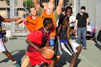 a basketball player being blocked by opponents during a street basketball tournament in madrid